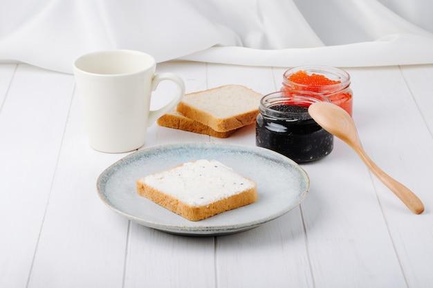 Vista frontale caviale nero e rosso con pane tostato con burro su un piatto con una tazza di caffè Foto Gratuite