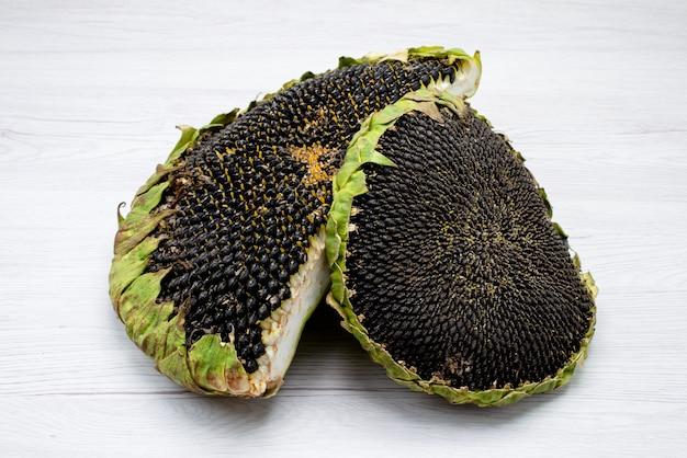 Una vista frontale semi di girasole neri freschi e gustosi spuntini di semi di girasole all'interno del grano delle coperture Foto Gratuite