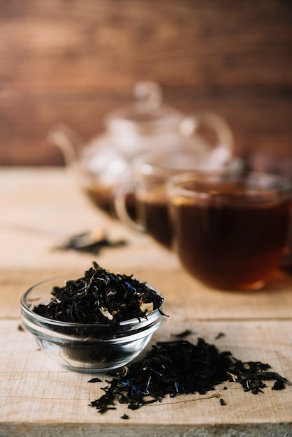 Front view black tea herbs with blurred background Free Photo