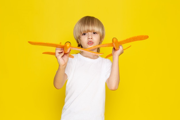 Front view blonde boy playing with orange toy planes in white t-shirt on yellow Free Photo