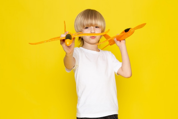 Front view blonde boy playing with toy orange planes in white t-shirt on yellow floor Free Photo