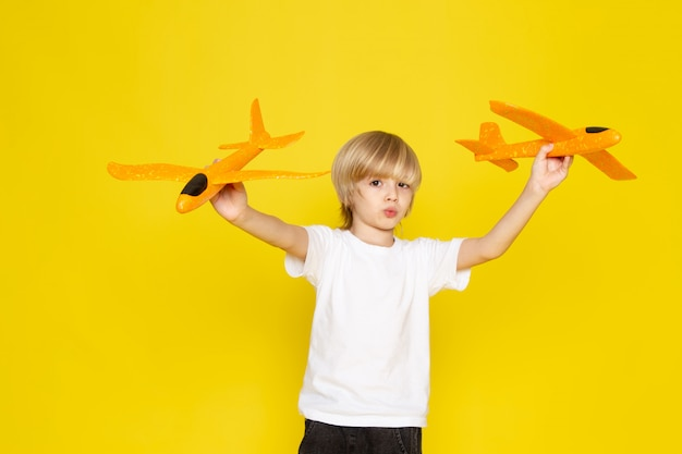 Front view blonde boy in white t-shirt playing with toy orange planes on the yellow floor Free Photo