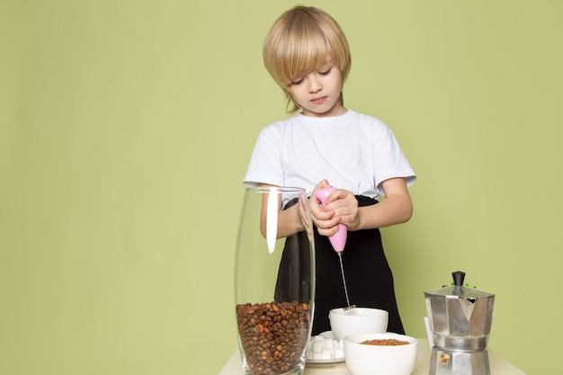 Un ragazzo biondo di vista frontale in maglietta bianca che prepara la bevanda del caffè sullo scrittorio color pietra Foto Gratuite