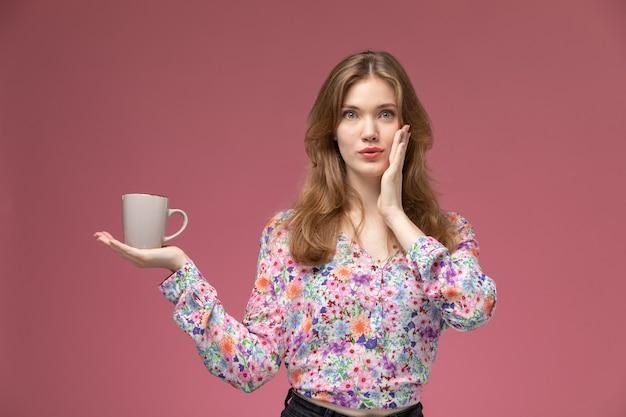 Signora bionda di vista frontale che dice qualcosa segretamente sulla sua tazza Foto Gratuite