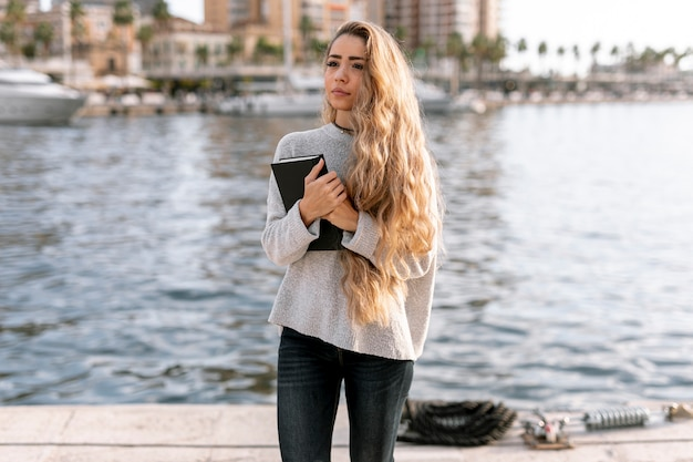 Front view blonde woman holding a book Free Photo
