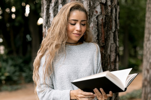 Front view blonde woman reading outside Free Photo