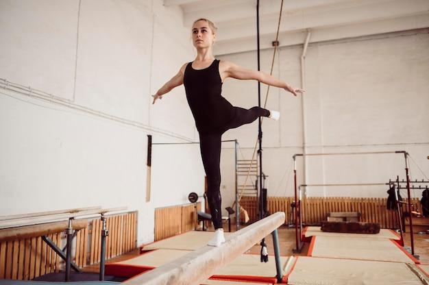 Вид спереди блондинка тренировки на бревне Бесплатные Фотографии