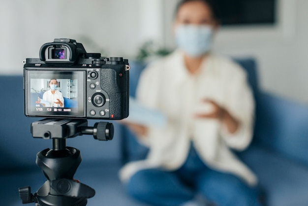 Front view blurry woman home streaming while wearing e face mask Free Photo