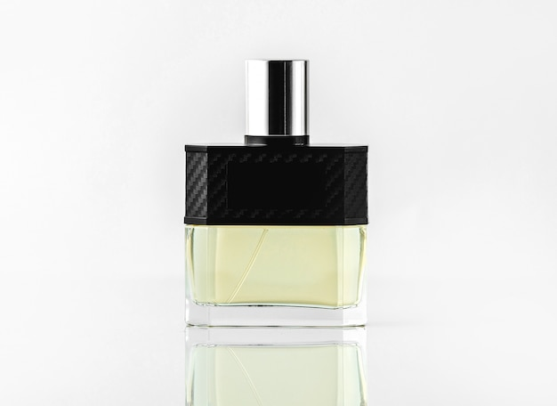 A front view bottle fragrance or parfume in designed colors on the white wall Free Photo