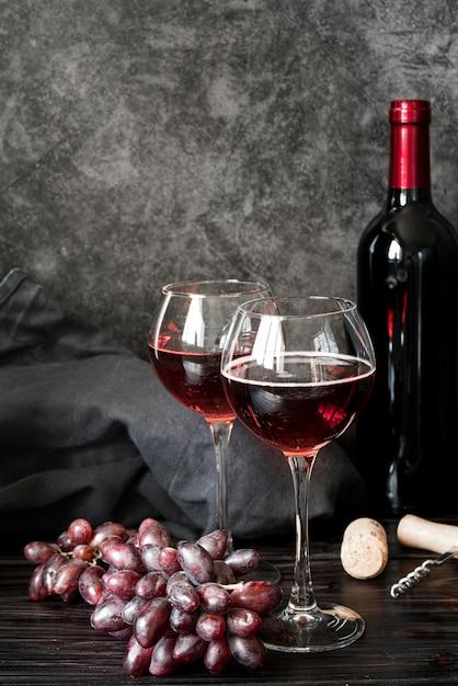 Бутылка вина и бокалы вид спереди Premium Фотографии