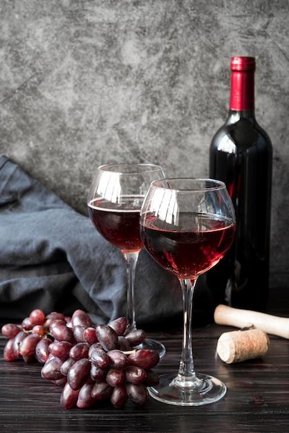 Bottiglia di vino di vista frontale con l'uva Foto Gratuite