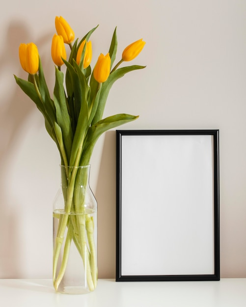 Front view bouquet of tulips in a vase with empty frame Free Photo