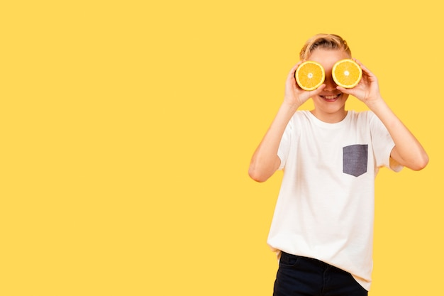 Front view boy covering eyes with orange slices Free Photo
