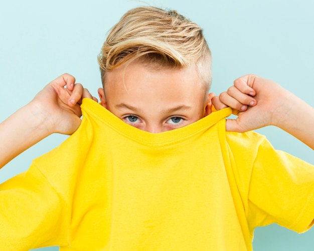 Front view boy covering his face with t-shirt Free Photo