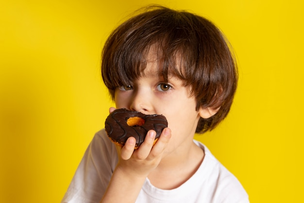 A front view boy eating choco donuts in white t-shirt on the yellow floor Free Photo