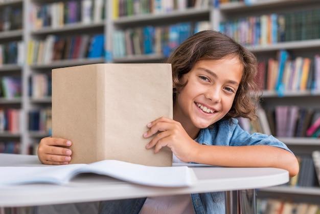 Мальчик вид спереди держит раскрытую книгу Бесплатные Фотографии