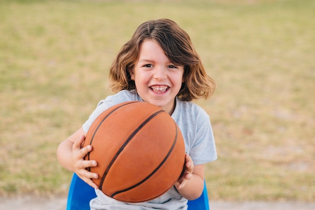 Front view of boy holding ball Free Photo