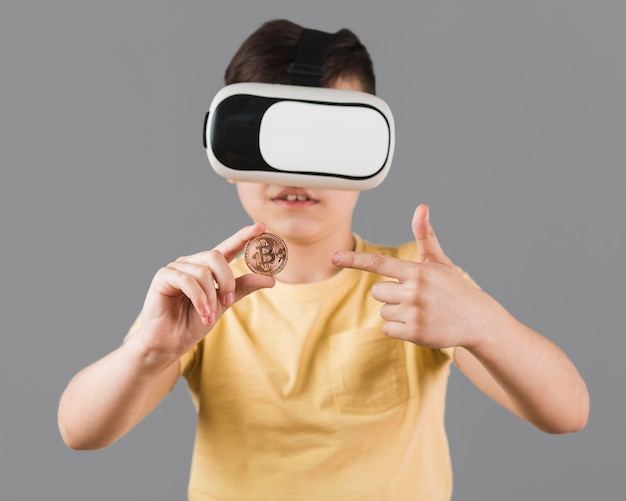 Front view of boy holding bitcoin while wearing virtual reality headset Free Photo