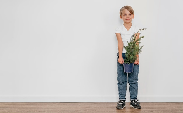 Front view of boy holding pot of plant with copy space Premium Photo