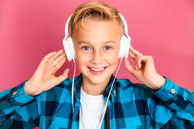 Front view boy listening music at headphones Free Photo