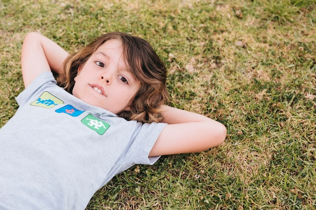 Front view of boy lying on grass Free Photo