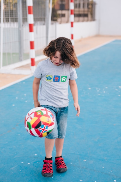 Front view of boy playing with ball Free Photo