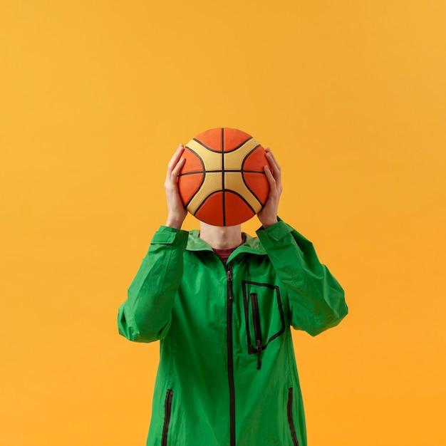 Мальчик вид спереди играет с баскетбольным мячом Бесплатные Фотографии