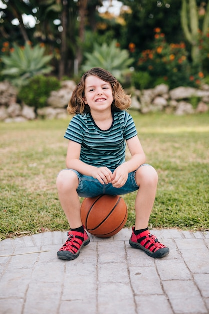 Front view of boy sitting on ball Free Photo