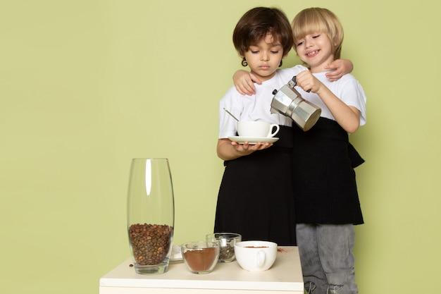 Una vista frontale ragazzi felici adorabili in magliette bianche sul pavimento color pietra Foto Gratuite