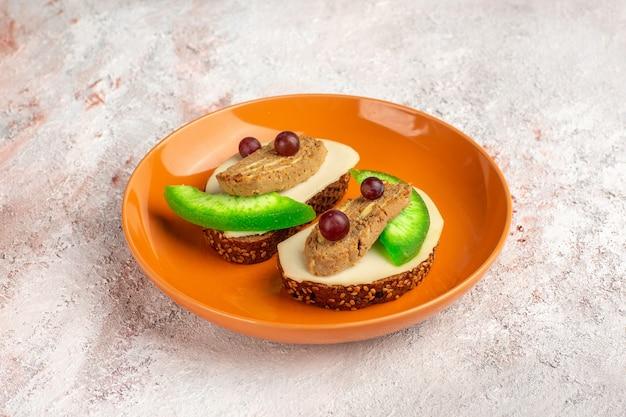 Toast di pane vista frontale con fette di patè e cetriolo all'interno del piatto arancione sulla superficie bianca Foto Gratuite
