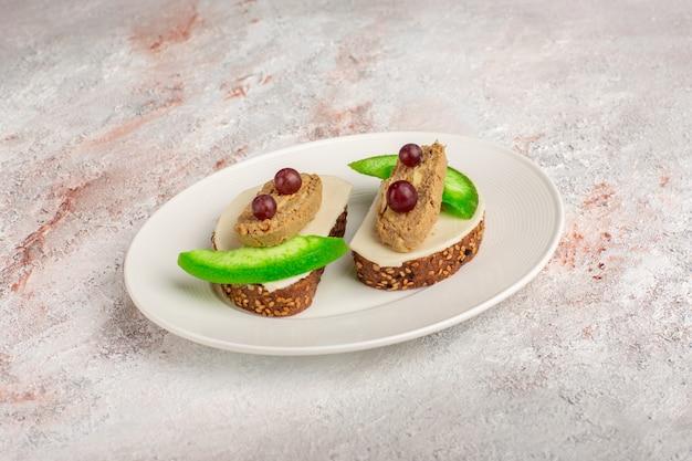 Toast di pane vista frontale con fette di patè e cetriolo all'interno del piatto sulla scrivania bianca Foto Gratuite