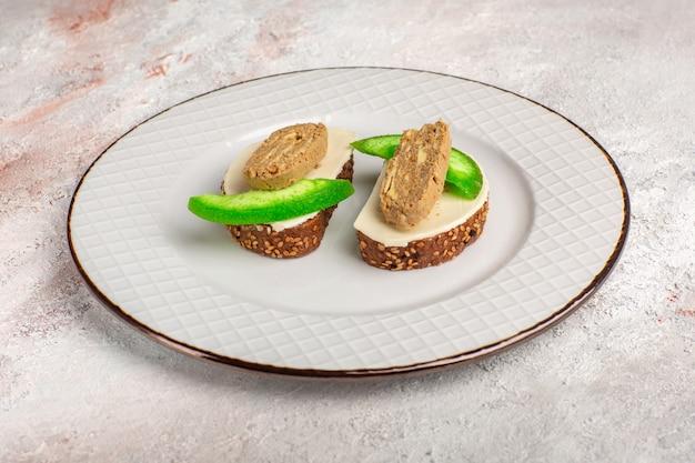 Toast di pane vista frontale con fette di patè e cetriolo all'interno della piastra sulla superficie bianca Foto Gratuite