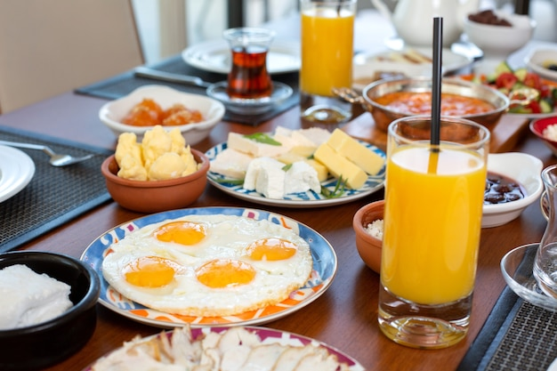 A front view breakfast table with eggs buns cheese and fresh juice in the restaurant during daytime food meal breakfast Free Photo