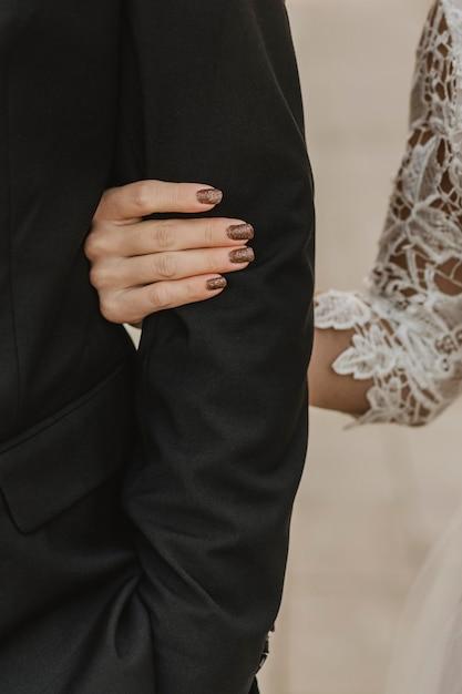 Vista frontale della sposa che tiene il braccio dello sposo Foto Gratuite