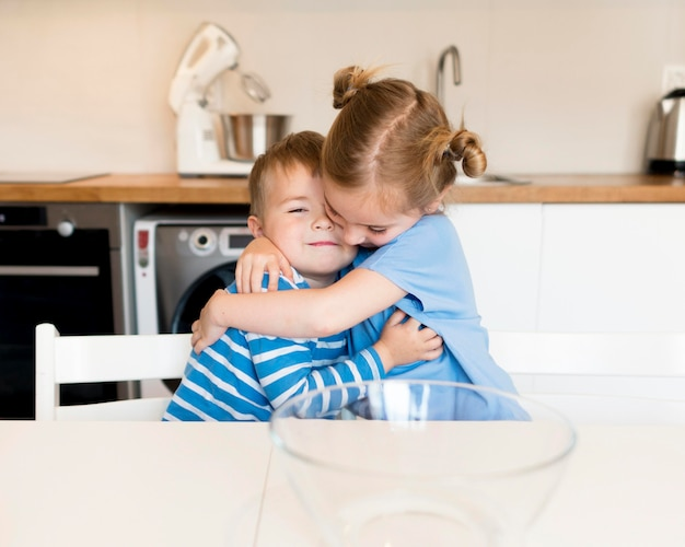 Front view of brother and sister hugging Free Photo