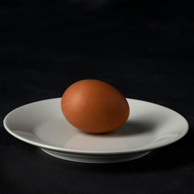 Коричневое яйцо на тарелке, вид спереди Бесплатные Фотографии