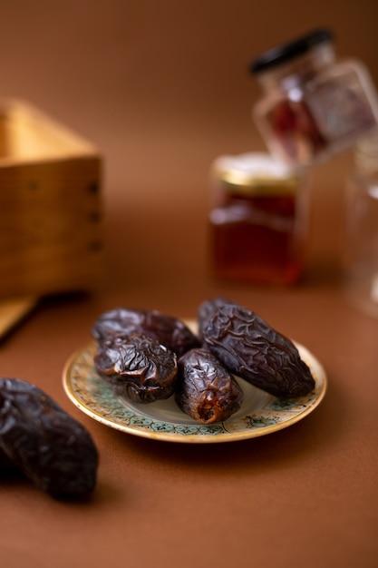 Вид спереди коричневая вкусная хурма внутри тарелки на деревянном столе Бесплатные Фотографии