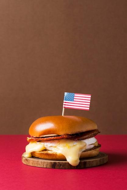 アメリカの国旗と木製の部分に正面のハンバーガー Premium写真