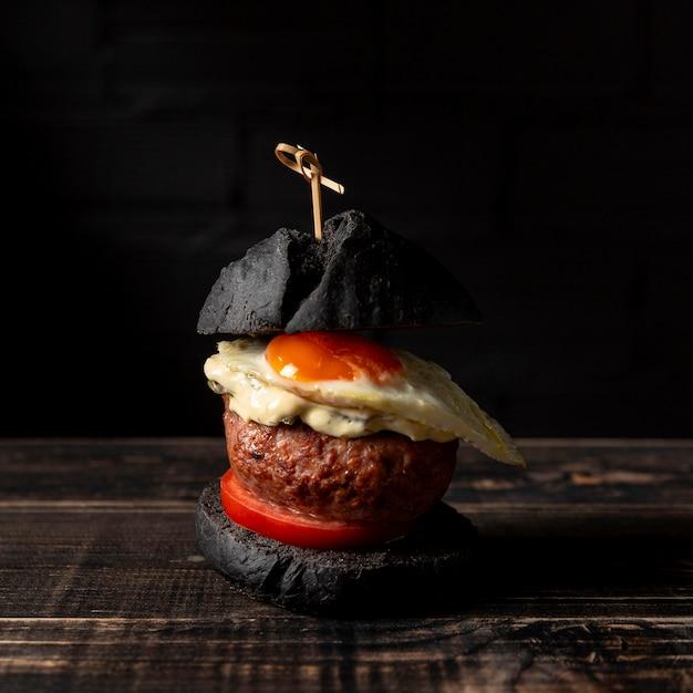 Hamburger di vista frontale con l'uovo sul tavolo Foto Gratuite