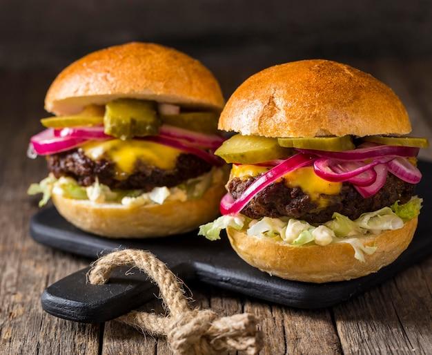 Гамбургеры, вид спереди, соленые огурцы и красный лук на разделочной доске Бесплатные Фотографии