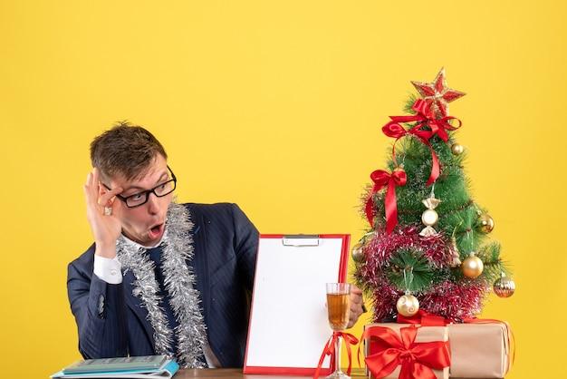 Vista frontale dell'uomo di affari che controlla la carta che si siede al tavolo vicino all'albero di natale e presenta sulla parete gialla Foto Gratuite