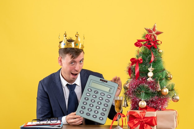 Front view of business man holding calculator sitting at the table near xmas tree and presents on yellow. Free Photo