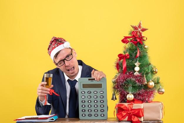 Vista frontale dell'uomo di affari che tostatura seduto al tavolo vicino all'albero di natale e regali su giallo Foto Gratuite