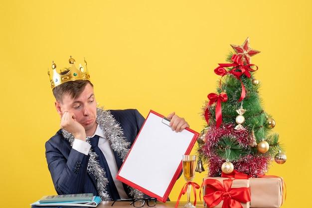 Vista frontale dell'uomo di affari con la carta di controllo della corona che si siede al tavolo vicino all'albero di natale e presenta su colore giallo Foto Gratuite