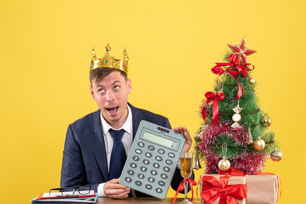 Front view of business man with crown holding calculator sitting at the table near xmas tree and presents on yellow Free Photo