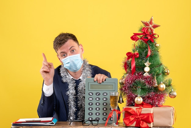 Front view of business man with mask pointing at calculator sitting at the table near xmas tree and presents on yellow Free Photo
