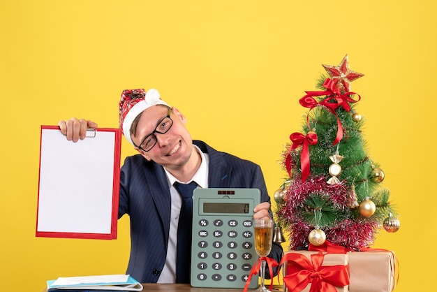 Front view of business man with santa hat holding clipboard and calculator sitting at the table near xmas tree and presents on yellow Free Photo