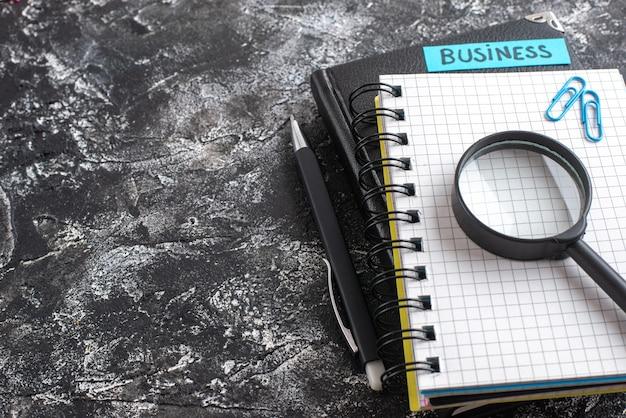 Nota di affari di vista frontale con blocchetti per appunti e lente d'ingrandimento su sfondo scuro Foto Gratuite