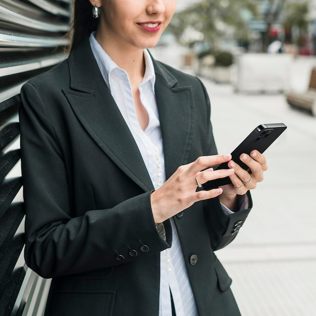 Front view business woman checking her smartphone Free Photo