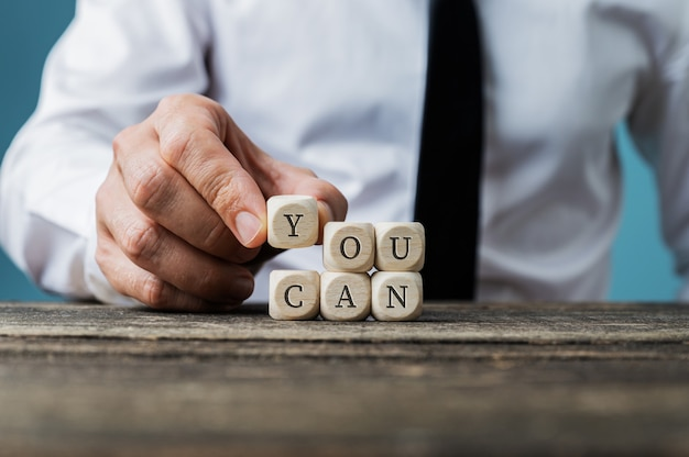 Front view of businessman assembling a you can sign spelled on wooden dices. Premium Photo